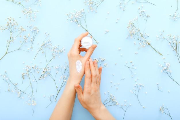 ハンドクリーム、パステルブルーの背景にオーガニックナチュラルクリーム化粧品を塗る女性の手。