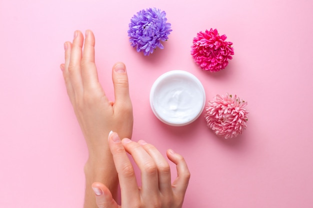 Hand cream and flowers. skin and hand care. moisturizing and eliminating the dryness of the hands skin