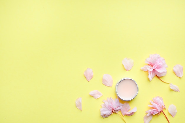 Hand cream, lip balm, and soap on a yellow background.