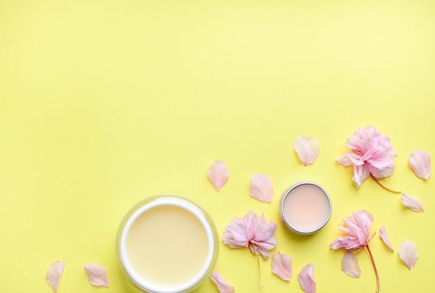 Hand cream, lip balm on a yellow background, flower petals.