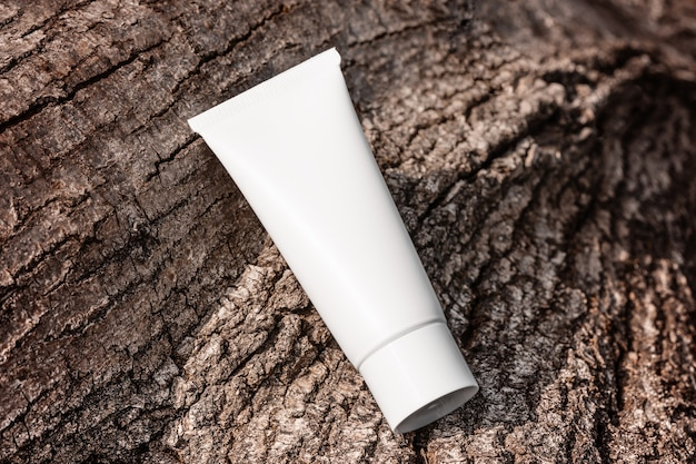 Hand cream moisturizer lotion in white plastic tube on tree bark top view antiage product template