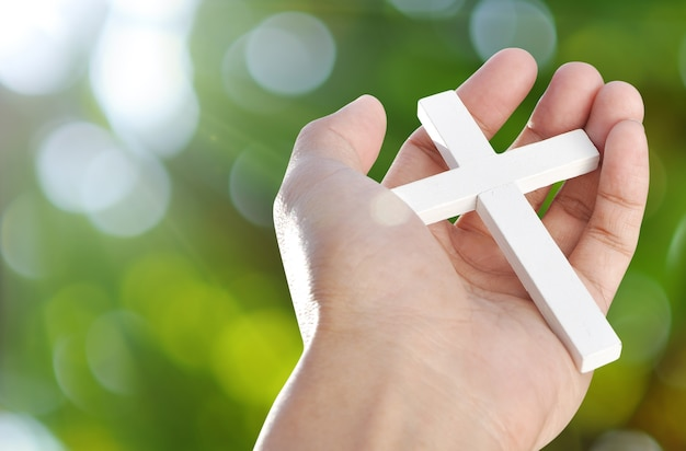 Hand and cross on light beams background , concept design