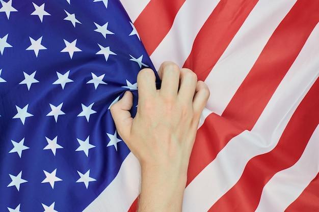 手をくしゃくしゃにしたアメリカのアメリカの国旗
