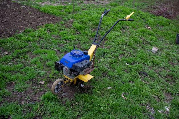 푸른 잔디에 손 경운기입니다. 모터 도구.