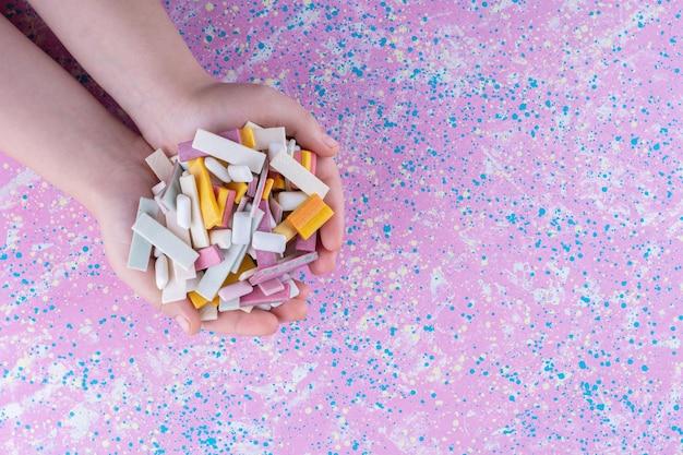 Рука, сложенная вместе, наполнена разноцветной жевательной резинкой на разноцветной поверхности