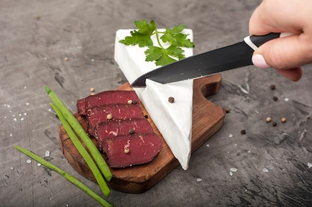 柔らかいチーズを白いカビで手でカットします。まな板に詰まった肉