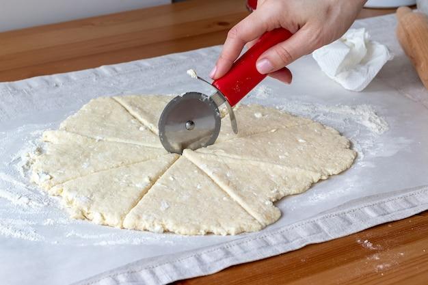 Раскатанное сырое творожное тесто вручную разрезает круглым ножом для пиццы на восемь треугольников