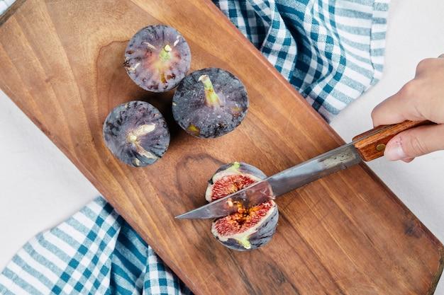 青いテーブルクロスで木製のまな板にいちじくを手で切る。