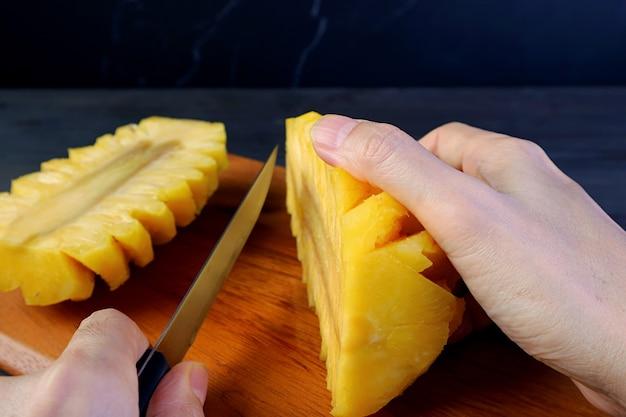 皮をむいた新鮮な熟したパイナップルを木の板で半分に手で切る