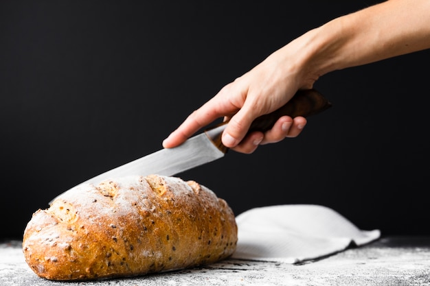 Hand cutting bread loaf with knife