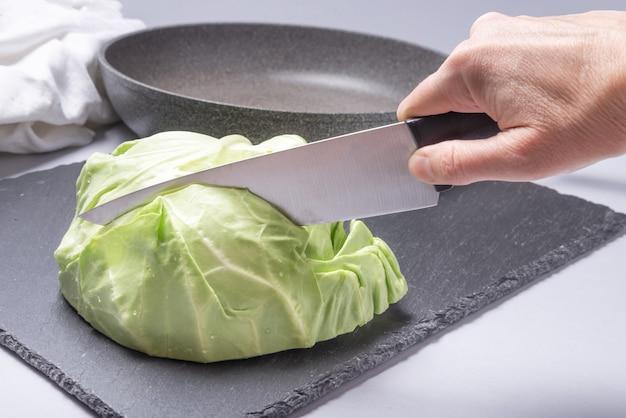 부엌 칼 검은 플라스틱 손잡이와 손 절단 양배추