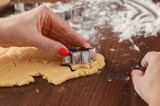 スターカッターで生姜のクッキー生地を手で形を切り抜く