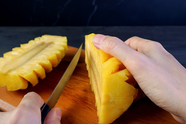 Hand cutting a peeled fresh ripe pineapple in half on a wooden board