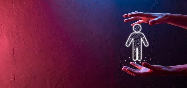 Hand on dark background holds human icon