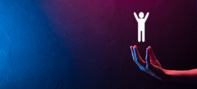 Hand on dark neon background holds human icon. banner with copy space and space for text.human resources hr management recruitment employment headhunting concept.