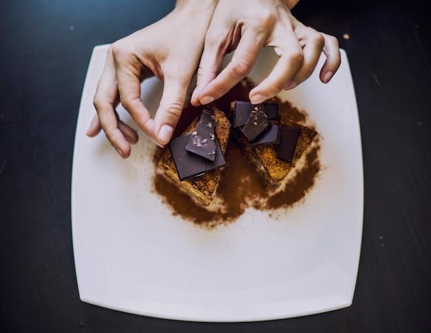 テーブルの上の女性の美しいチョコレートケーキのクローズアップで飾られた手