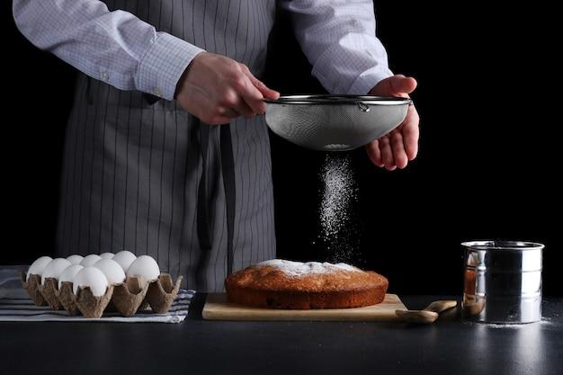 Рука украшения сита сахарной пудры пирога на темном фоне
