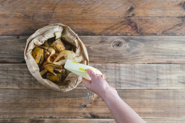 Hand depositing fruit scraps in paper bag with compostable fruit peels.