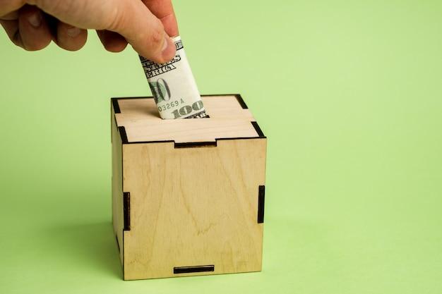 Hand depositing hundred dollar bill into moneybox
