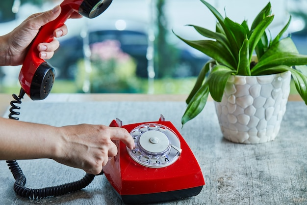 Hand dialing the number on telephone in the marble surface