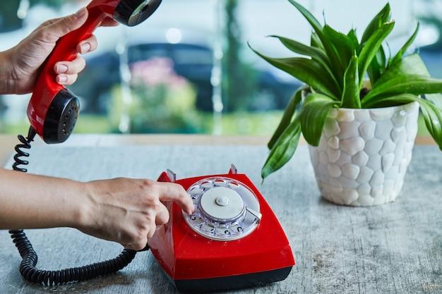 大理石の表面で電話で番号を手でダイヤルする