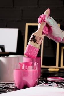 ピンクのペンキでペイントブラシを浸す手