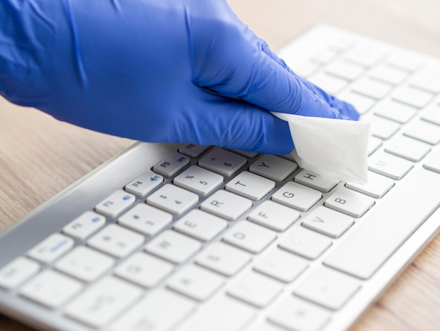Hand disinfecting keyboard surface with napkin