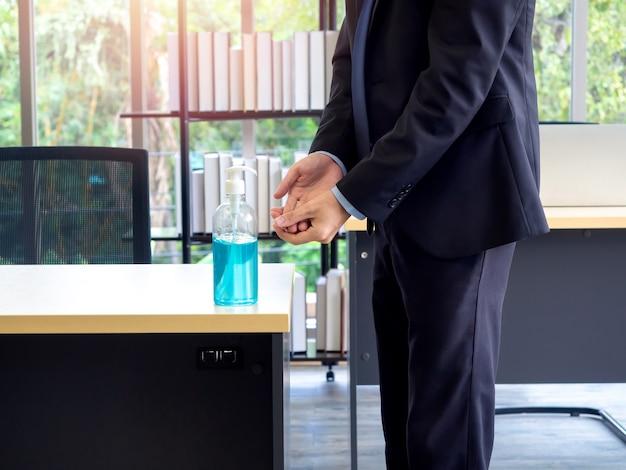 アルコールジェルによる手指消毒。オフィスのテーブルで消毒剤を使用してビジネスマンの手