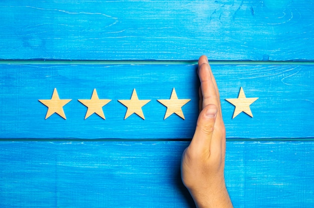 The hand divides the fifth star from the four others. rating 5 stars, 4 stars. overview