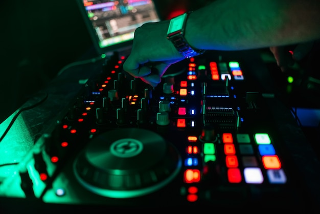 Hand of dj controlling and moving the mixers in music remote