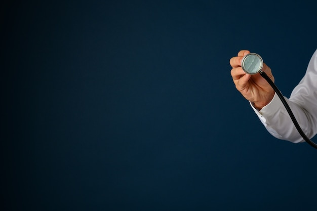 Hand of a doctor holding stethoscope disk towards the camera. over blue background with copy space.