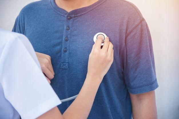 손 의사 또는 간호사 여자 격리 된 청진기를 사용 하여 환자 남자를 검토합니다.