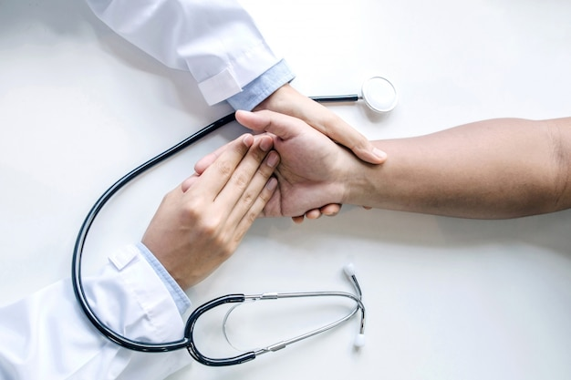 Hand of doctor reassuring male patient and stethoscope