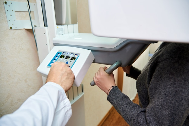 Hand doctor in a white coat presses the control buttons