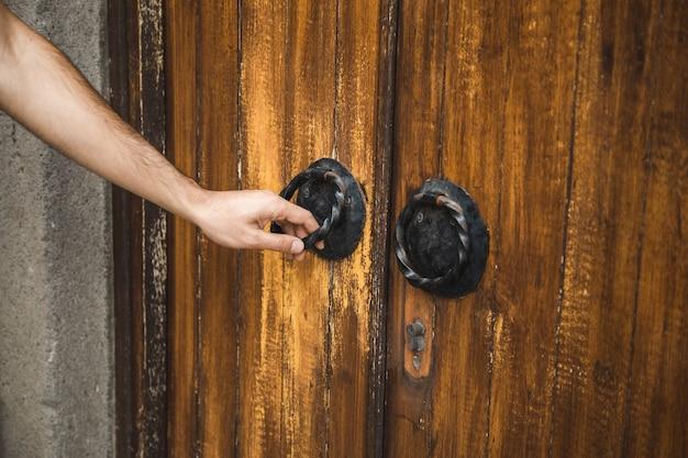 오래 된 교회 문에 손 문 두 들기는 사람