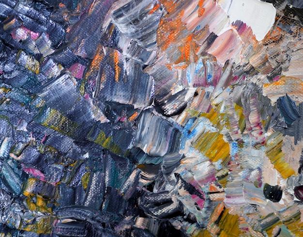 手は、テクスチャとカラフルな絵画の抽象的な背景を描きます。