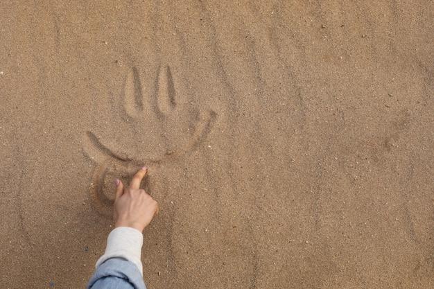 砂漠の砂で美しいかわいい笑顔を描く手
