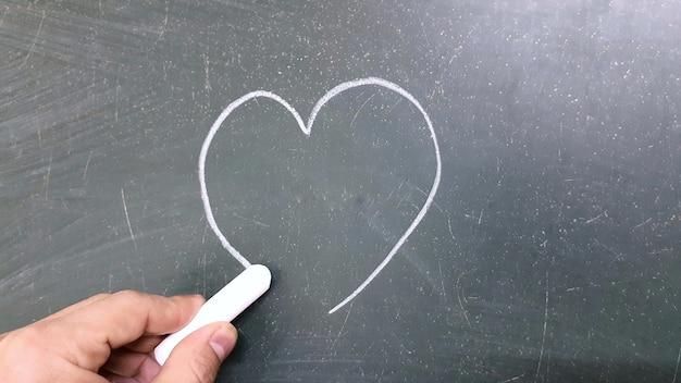 Рука рисунок сердце мелом на доске в школе