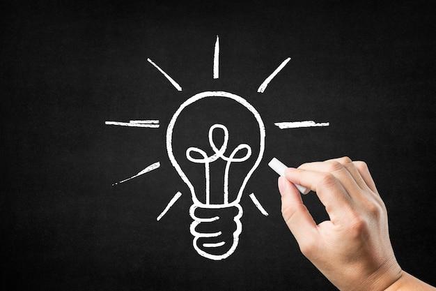 Hand drawing a light bulb on a blackboard