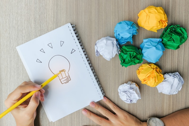 Hand drawing light bulb or lamp with colorful crumpled paper on wooden table