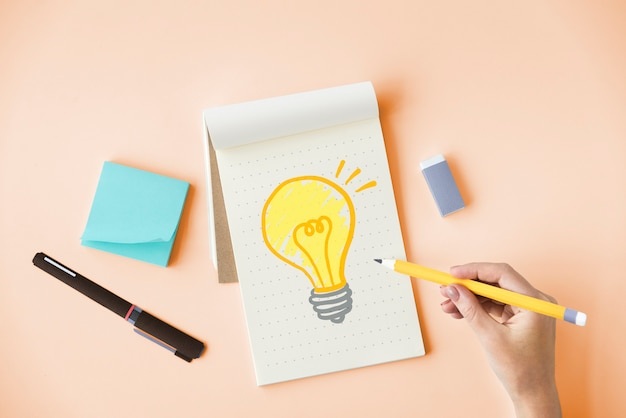 Hand drawing a light bulb on a notepad