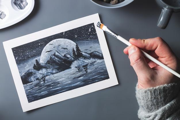회색 배경에 브러시로 흑백으로 달과 산을 그리는 손. 단색 평면 배치