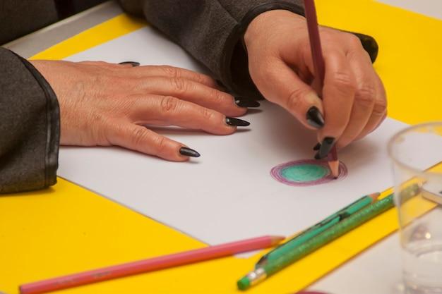 Рука рисунок на белом листе цветными карандашами,