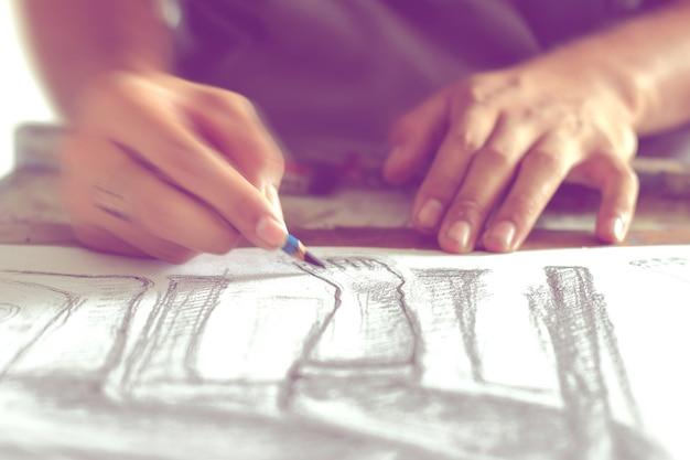 Рука рисует человеческую фигуру карандашом, размытым движением.