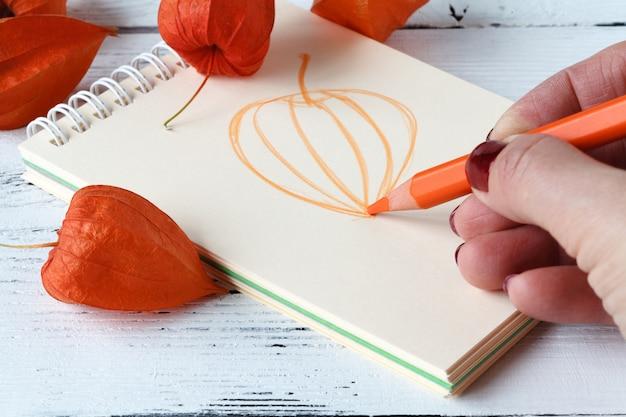 ペンとスケッチブックで描く手。紅葉