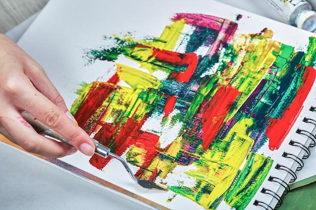 白いテーブルの上のペイントチューブと手描きの抽象芸術。