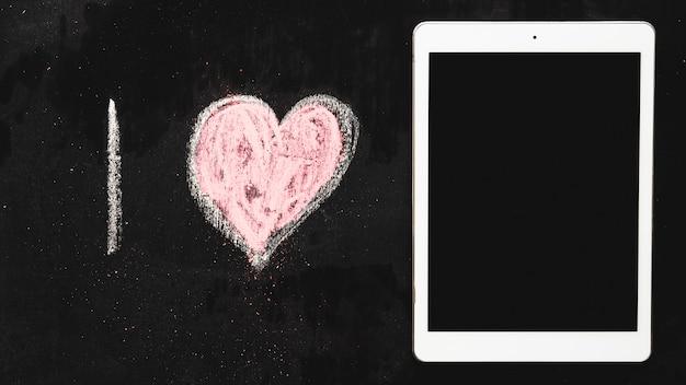 Hand drawn alphabet i and heart shape near digital tablet on chalkboard