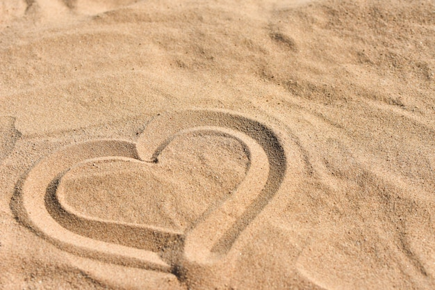 Hand drawn heart on sea sand on the beach