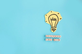 Hand drawn idea light bulb outside the box text made with blocks on blue background