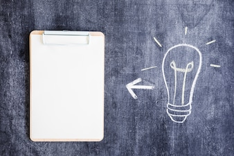 Hand drawn light bulb and clipboard on blackboard